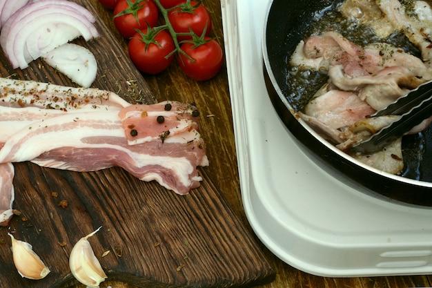 自家製料理。キッチンパンで焼く豚肉または牛肉のブリスケットは、トングでひっくり返されます。トマト、玉ねぎ、ニンニク。