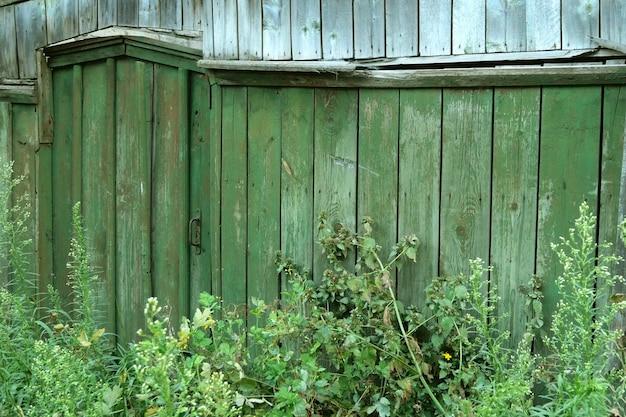 閉じられた、草で覆われたドアまたは田舎の木製の緑のフェンスの改札口。田園風景。