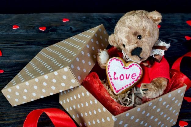 Милый плюшевый мишка сидит в подарочной коробке с сердцем.