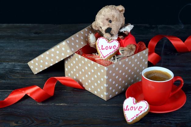 Милый плюшевый мишка сидит в подарочной коробке с сердцем. в руках печенье.