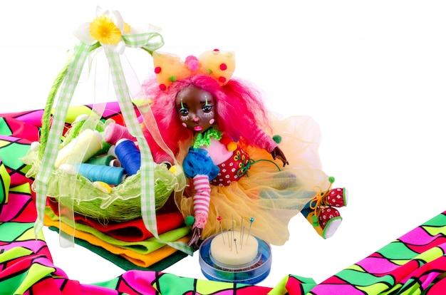 Симпатичная кукла сидит сверху на кусочки разноцветной ткани, рядом с ней булавки, разноцветная ткань.