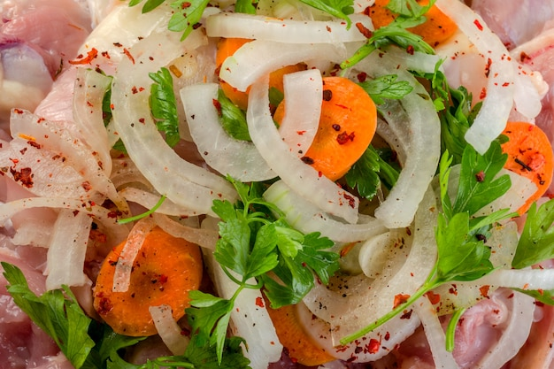 新鮮な生の鶏肉とタマネギ、ニンジン、スパイス、調理用に準備された野菜。閉じる。