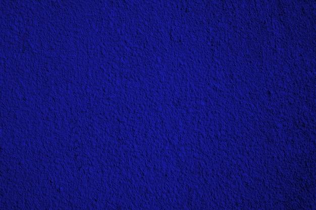 大まかなネイビーブルー塗装石膏または漆喰壁。トーン。コピースペースで抽象的なグランジ背景。
