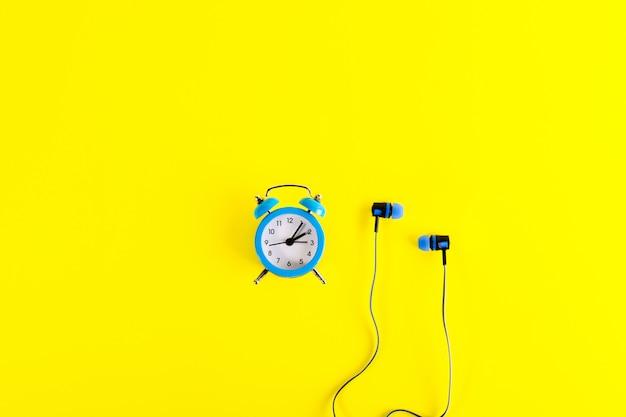 小さな青いクラシックスタイルの目覚まし時計と明るい黄色の背景に青いイヤホン。