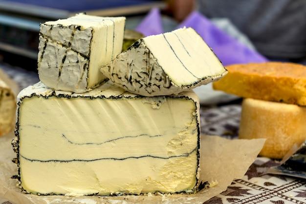 マーケットカウンターにある様々な種類のチーズの全体とノッチ頭。チーズのコンセプト
