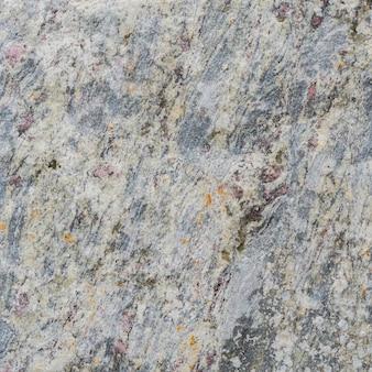 ピンクの斑点がある石の灰色の質感。