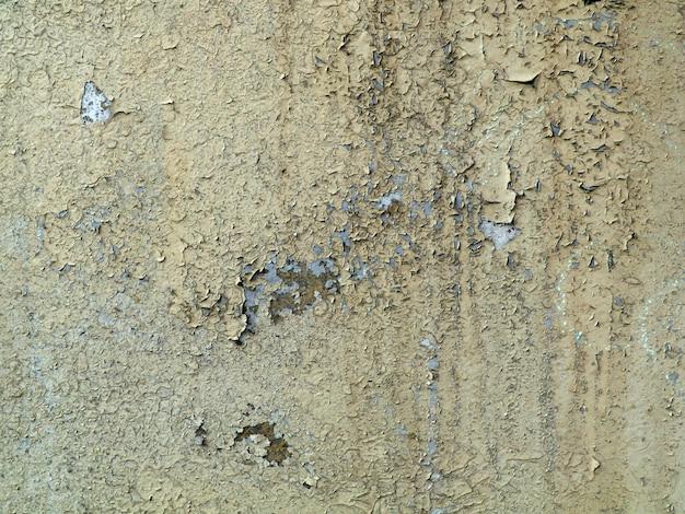 Серая потрескавшаяся краска на старой стене