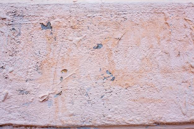 Розовая потрескавшаяся краска на старых разрушенных стенах домов