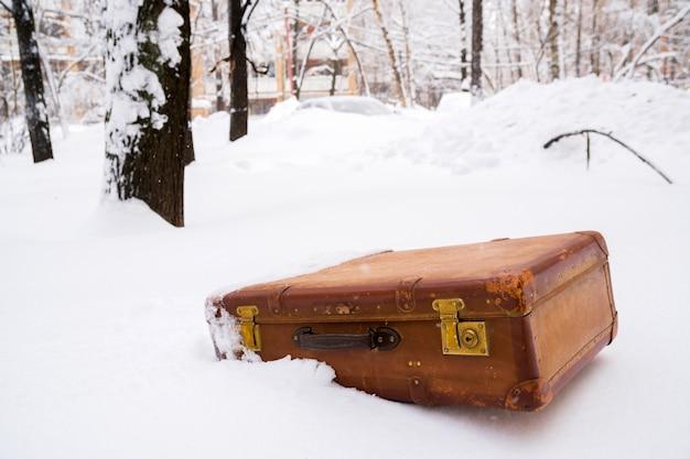 雪の中に古い革の茶色のスーツケース