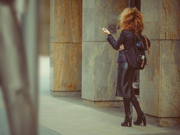 彼女の手にタバコを持って赤髪、巻き毛の女性