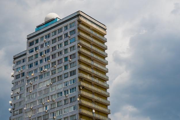 空を背景にガラス製のモダンな高層ビル