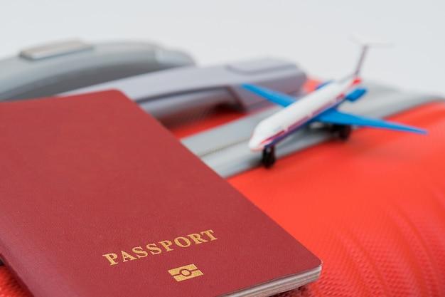 Красный паспорт и модель самолета лежат на красном чемодане.