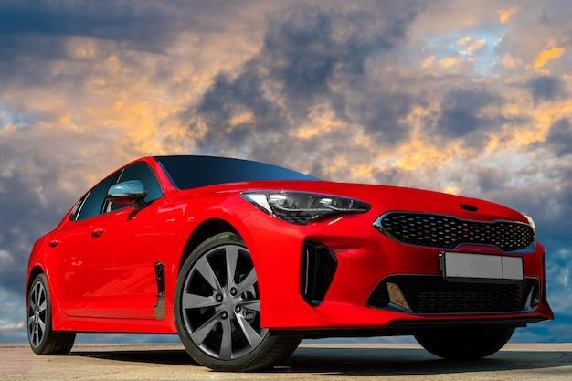 夕方の空を背景に赤い車。