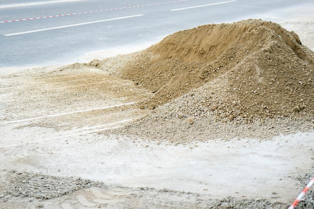 灰色の砂利の山。市内の道路の修理