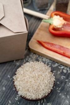 Азиатский белый рис с овощами в бумажной коробке.