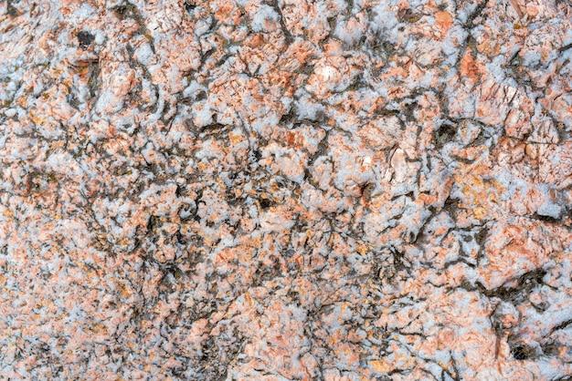 割れた石の表面。ピンクの花崗岩のテクスチャ。