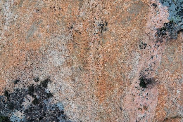 石のテクスチャ。ピンクの花崗岩の表面。