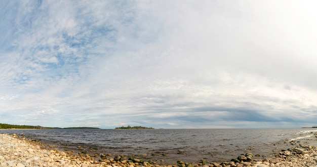 湖の小石のビーチの上の空。