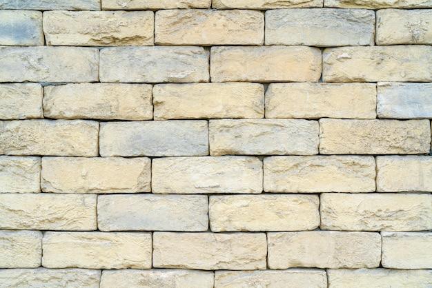 砂岩と石灰岩で作られた黄色のレンガのテクスチャ。家の壁。