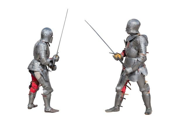 Рыцари в доспехах. средневековые рыцари в железных доспехах держат в руках мечи. дуэль средневековых воинов. битва двух рыцарей на мечах.