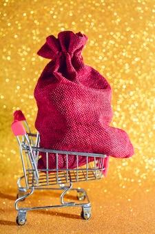 Рождество золотое. подарок на рождество в тележке супермаркета.