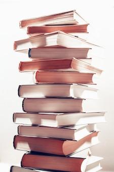 Вертикальная башня книг. стопка книг в библиотеке. научные, образовательные и художественные книги. образование и обучение.
