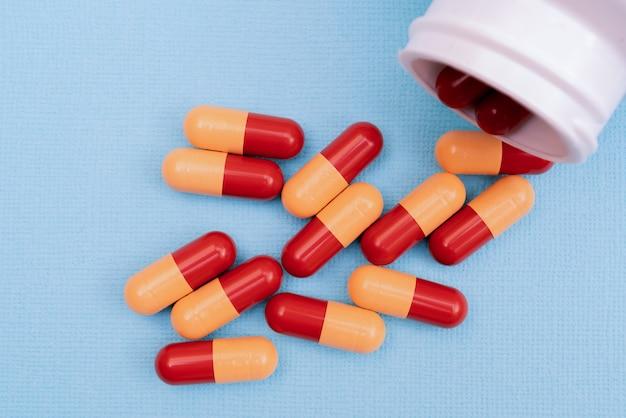 Таблетки для лечения заболевания. таблетки или капсулы. лекарственный рецепт для медикаментозного лечения. фармацевтический препарат, лекарство в таре для здоровья. продажа антибиотика.