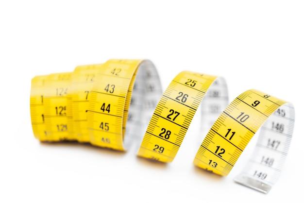 白い背景の上の黄色の測定テープ。長さと円周の測定。体重を減らして太ります。