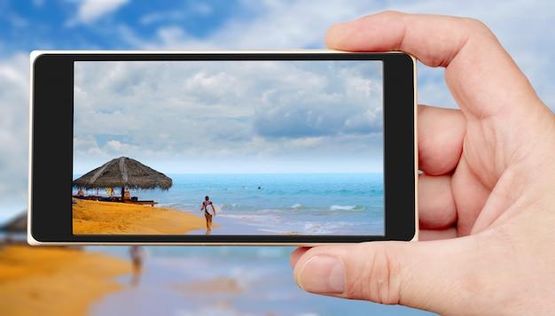Песчаный океанский пляж на экране смартфона. солнечный день в тропиках.