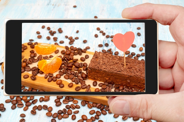 スマートフォンの画面に新鮮なチョコレートケーキ。