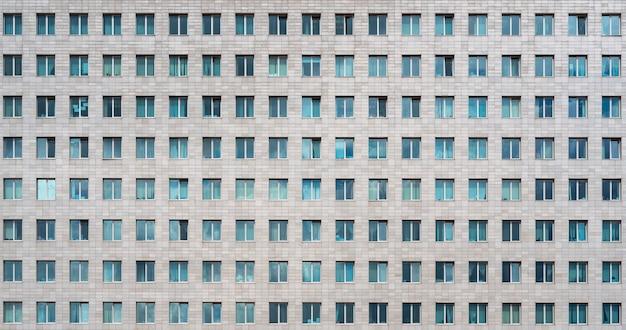 Современное офисное здание. окна многоэтажного небоскреба. ряды одинаковых окон.
