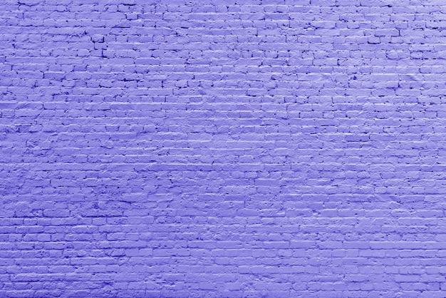 Старая винтажная фиолетовая предпосылка текстурированная кирпичной стеной.