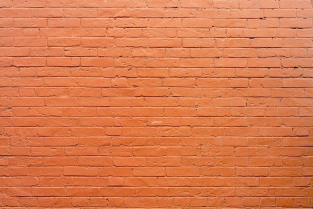 Старая винтажная красная предпосылка текстурированная кирпичной стеной.