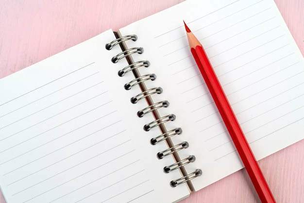 ノートのための赤い鉛筆とノートブック。