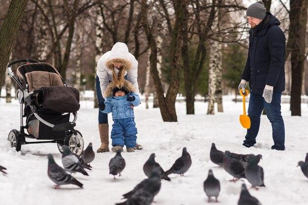 冬の公園を歩いて幸せな若い家族