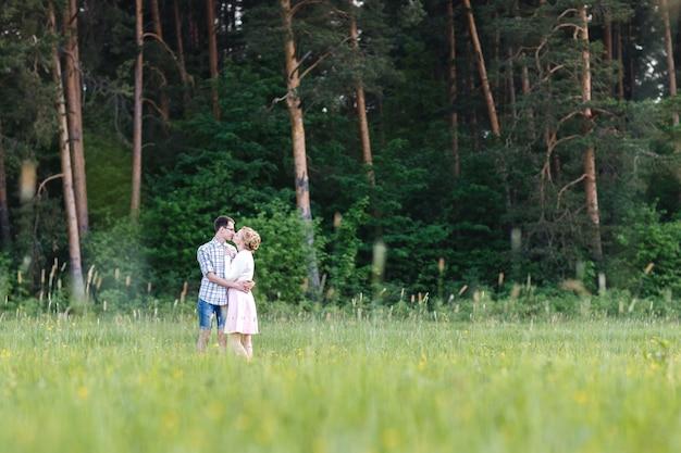 若いカップルが森の近くの畑を歩きます。幸せな恋人たちは抱きしめてキスをする。
