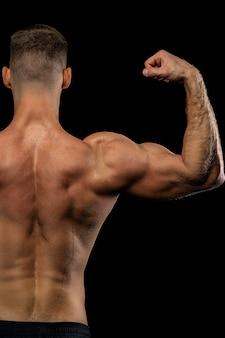 強力な筋肉アスリートが黒い壁の横に背中を披露