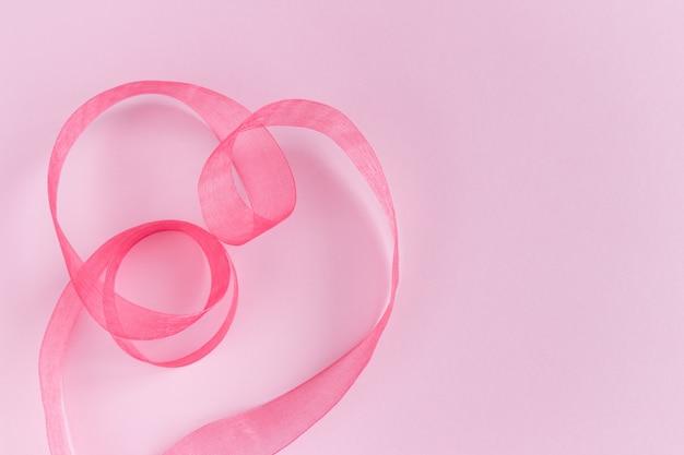 ピンクの背景にハート形のお祝いピンクサテンシルクリボン波。休日の装飾。プレゼント包装。テキストのコピースペース