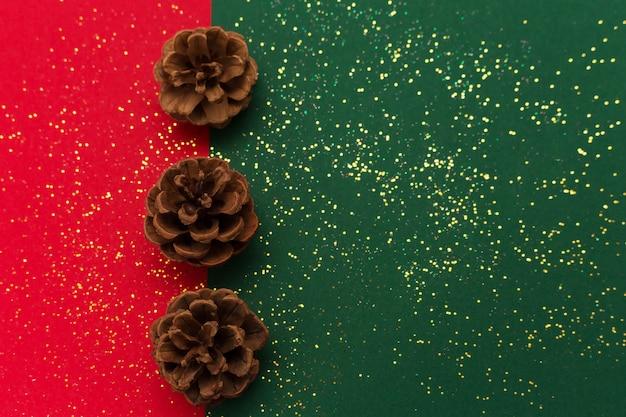 Рождество с шишками и золотой блестящий блеск на традиционный зеленый и красный фон.