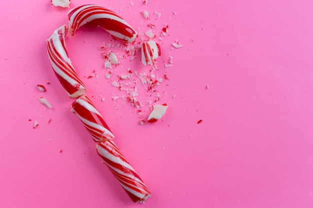 ピンクの背景に壊れたキャンディー杖。