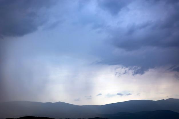 Дождь из облаков постепенно покрывает горы.