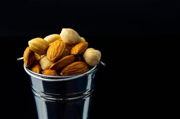 Смесь орехов в маленьком железном ведре и корзине для покупок