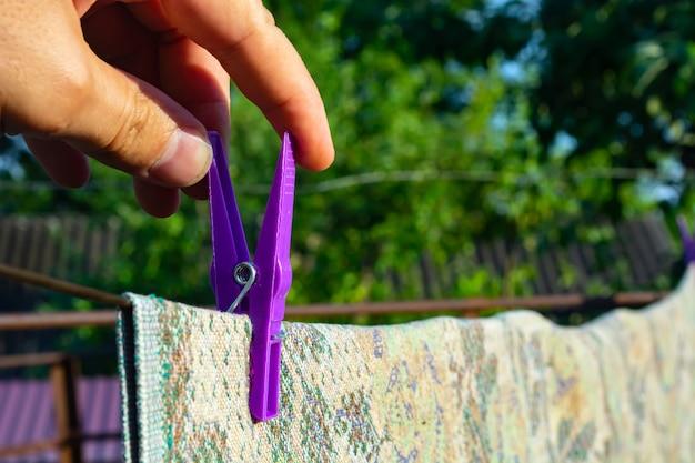 Рука держит прищепку на веревке