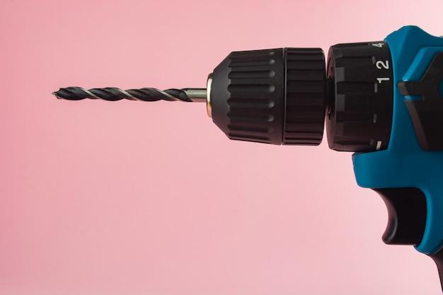 Инструмент для сверления на розовом фоне