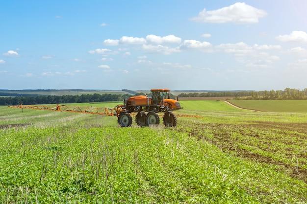 自走式噴霧器は、雲がある青空の下の畑で働く