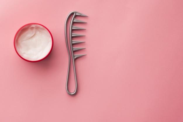 Маска для волос и расческа на розовом фоне. уход за волосами. ламинирование волос. молоко в косметических баночках,