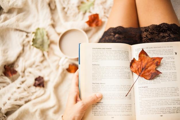 Осенний натюрморт. вид сверху. девушка читает открытую книгу, сидя на пледе