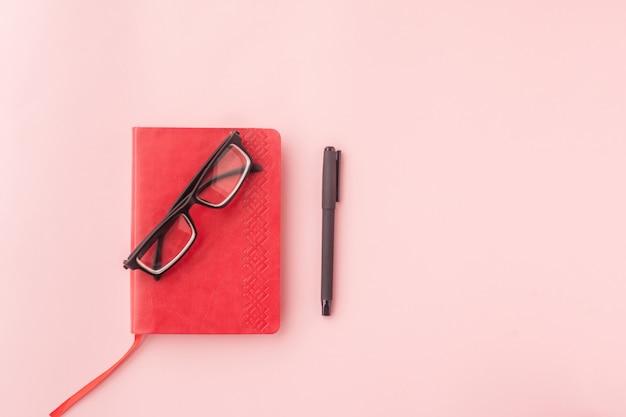 Красный дневник, ручка и очки вид сверху на розовом фоне. выборочный фокус.