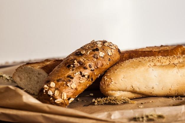 木製のテーブルの上に横たわるさまざまな種類のパンのミックス