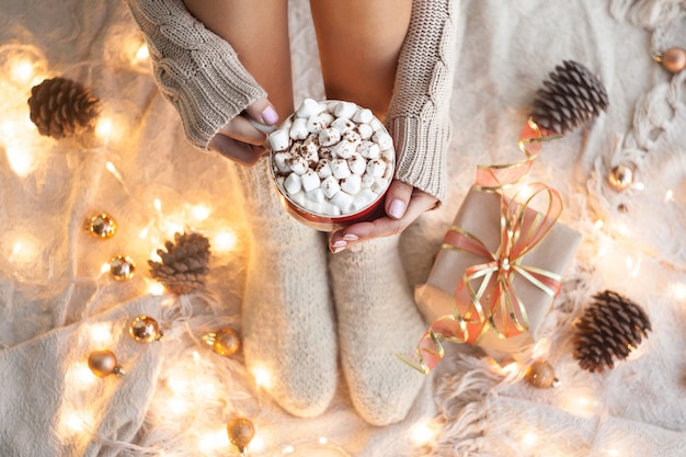 Женщина руки, проведение чашку кофе. уютная концепция зимы. горячий шоколад или какао с маркой